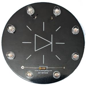 """A black circular circuit board with eight LEDs outlining the edge and a resistor along the bottom. Just beneath the resistor is the text """"www.mrblinkbling.com GET NOTICED!"""""""